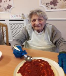 Doris spreading tomato sauce
